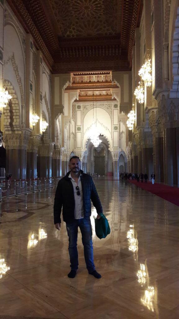 No interior da Mesquita Hassan II com a sacolinha com meu tênis nas mãos.