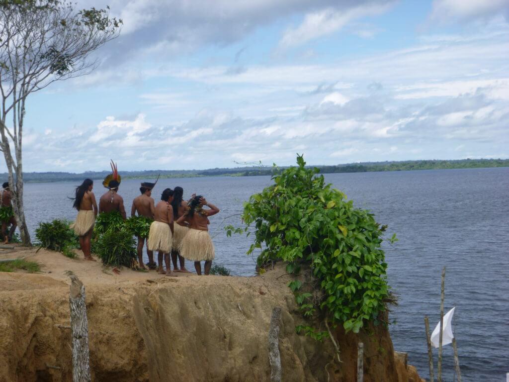 Os índios recepcionando os turistas às margens do Rio Negro