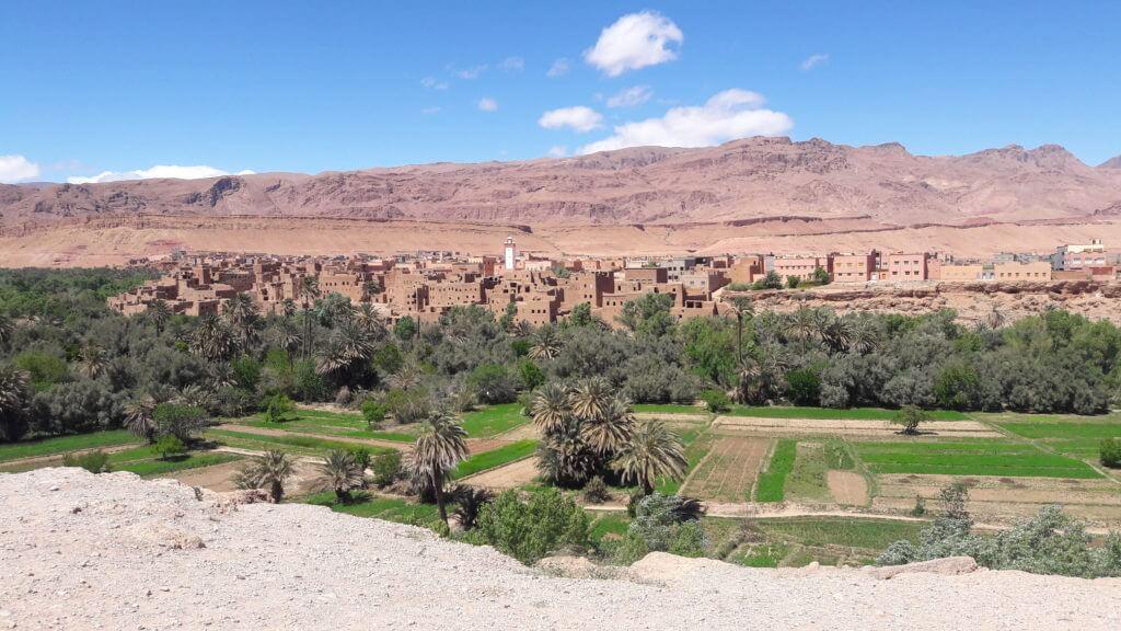Extensas faixas de plantação contrastando com a aridez vermelha das cidades
