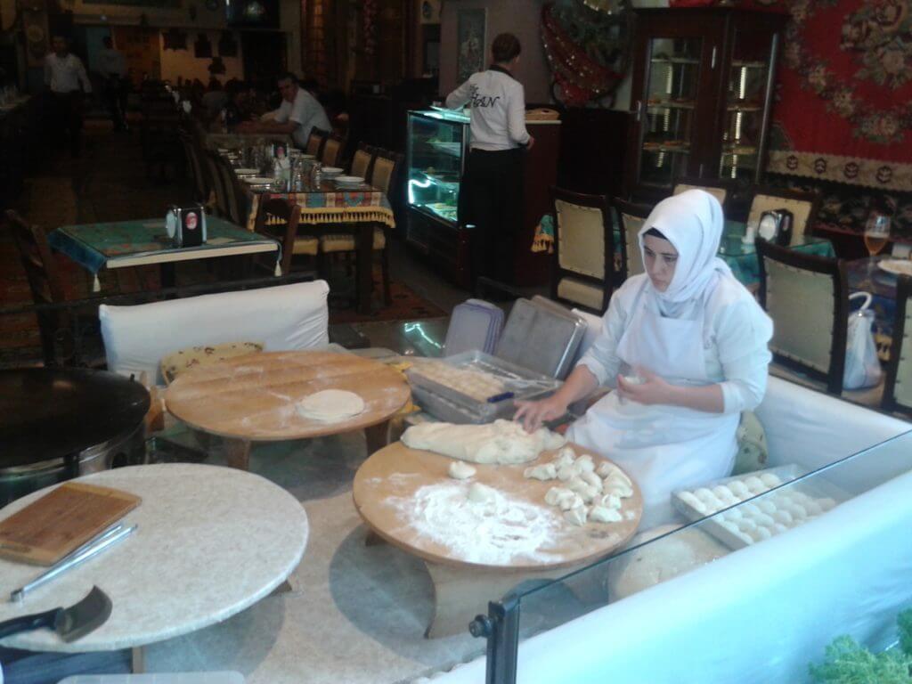 As mulheres preparando o pão na entrada dos restaurantes
